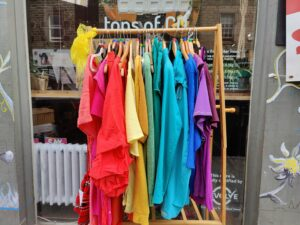 A rail of colourful clothes sorted in rainbow order outside Shrub co-op
